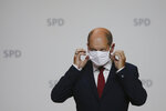 German Finance Minister Olaf Scholz fixes his face mask after a news conference in Berlin, Germany, Monday, Aug. 10, 2020. Olaf Scholz announces that he will run for the for the Social Democratic Party as chancellor candidate at next year's general elections in Germany.(AP Photo/Markus Schreiber)