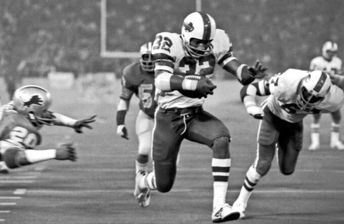 FILE - In this Nov. 25, 1976 file photo, Buffalo Bills' O.J. Simpson rushes through a large hole in the center of the Detroit Lions' defensive line to score on a 12-yard run for his second touchdown of the NFL football game in Pontiac, Mich. For the first time in 42 years, the Bills have a player wearing Simpson's former No. 32. Running back Senorise Perry wore the jersey number at Buffalo's spring practices this week. (AP Photo/File)