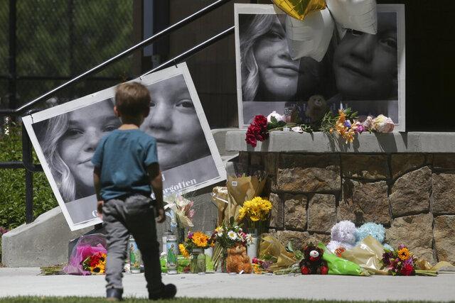 A boy checks out a memorial for Tylee Ryan, 17, and Joshua