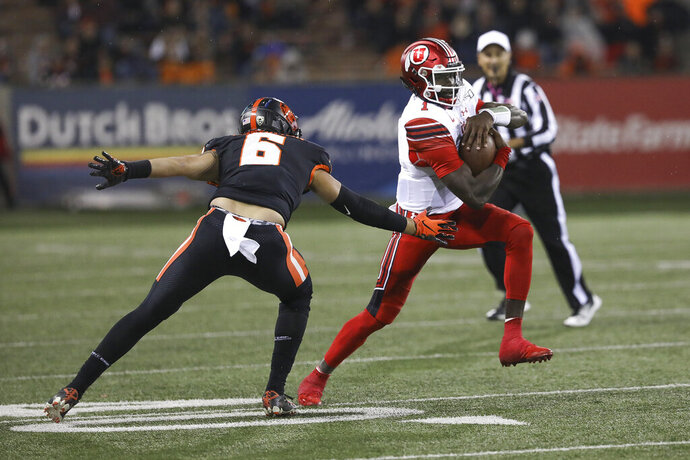 Utah quarterback Tyler Huntley (1) dodges Oregon State outside linebacker John McCartan (6) during the second half of an NCAA college football game in Corvallis, Ore., Saturday, Oct. 12, 2019. Utah won 52-7. (AP Photo/Amanda Loman)