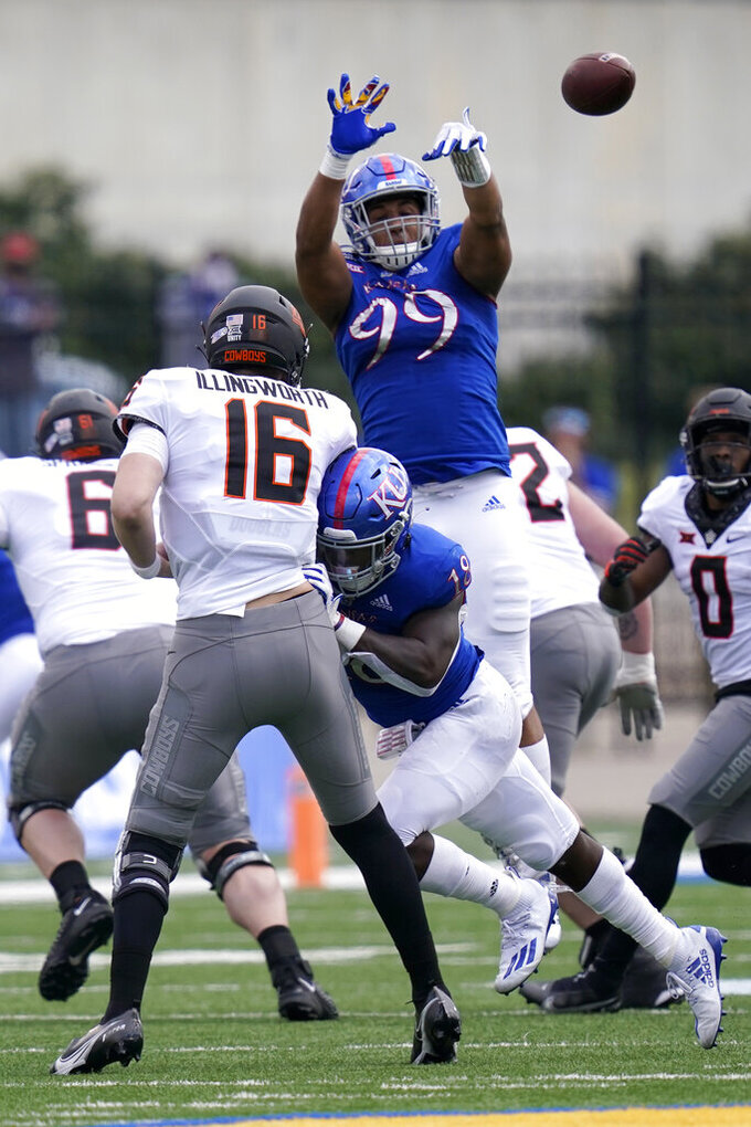 Kansas defensive lineman Malcolm Lee (99) blocks a pass by Oklahoma State quarterback Shane Illingworth (16) during the first half of an NCAA college football game in Lawrence, Kan., Saturday, Oct. 3, 2020. (AP Photo/Orlin Wagner)