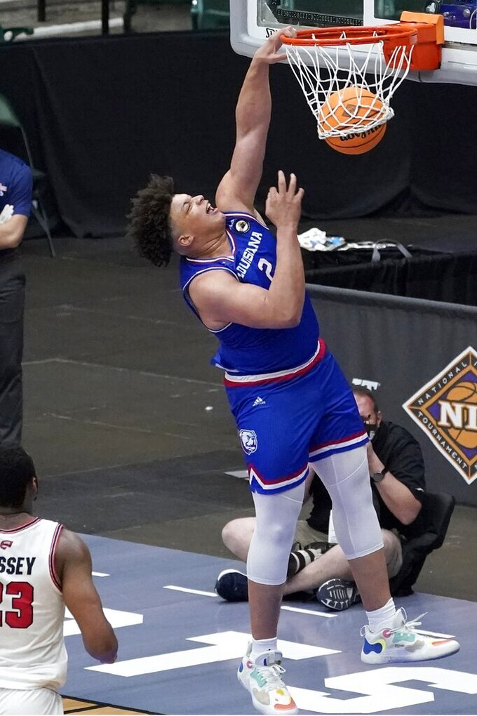 Louisiana Tech forward Kenneth Lofton Jr. dunks on a breakaway as Western Kentucky's Charles Bassey watches during the second half of an NCAA college basketball game in the quarterfinals of the NIT, Thursday, March 25, 2021, in Frisco, Texas. (AP Photo/Tony Gutierrez)