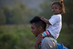 A Central American migrant, part of the caravan hoping to reach the U.S. border, carries a child on his shoulders as they move on a road in Escuintla, Chiapas State, Mexico, Saturday, April 20, 2019. Thousands of migrants in several different caravans have been gathering in Chiapas in recent days and weeks. (AP Photo/Moises Castillo)