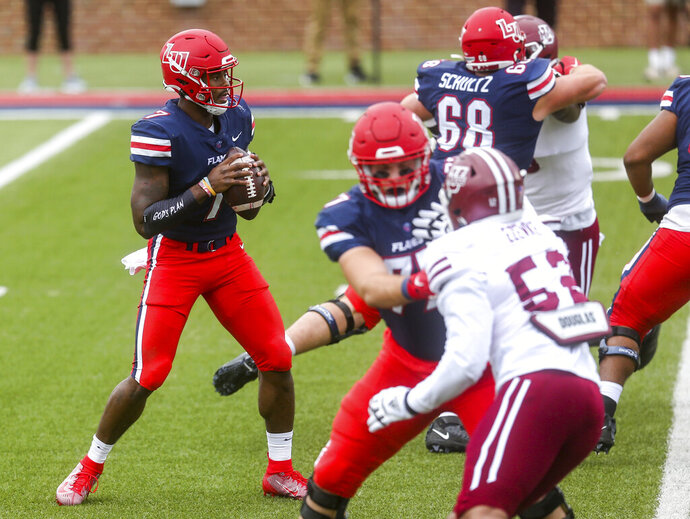 Liberty quarterback Malik Willis (7) looks to make a pass during the first half of a NCAA college football game against Massachusetts on Friday, Nov. 27, 2020, at Williams Stadium in Lynchburg, Va. (AP Photo/Shaban Athuman)