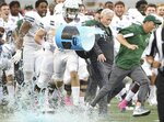 Tulane coach Willie Fritz, right, outruns the beverage shower as players celebrate after winning the Cure Bowl NCAA college football game against Louisiana in Orlando, Fla, on Saturday, Dec. 15, 2018. (Stephen M. Dowell/Orlando Sentinel via AP)