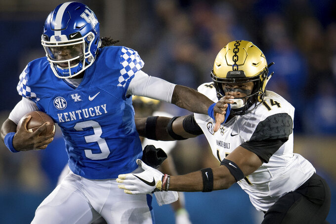 Kentucky quarterback Terry Wilson (3) is tackled by Vanderbilt defensive back Max Worship (14) during the second half of an NCAA college football game in Lexington, Ky., Saturday, Oct. 20, 2018. Kentucky won, 14-7. (AP Photo/Bryan Woolston)