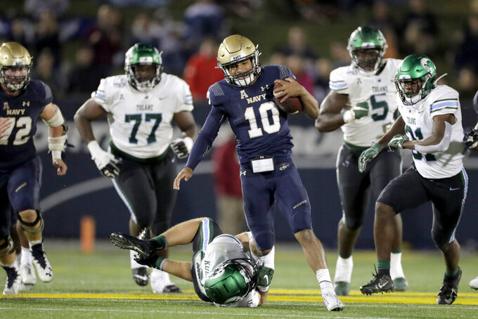 Navy quarterback Malcolm Perry (10) avoids a tackle by Tulane safety Chase Kuerschen while running with the ball during the second half of an NCAA college football game, Saturday, Oct. 26, 2019, in Annapolis. Navy won 41-38. (AP Photo/Julio Cortez)