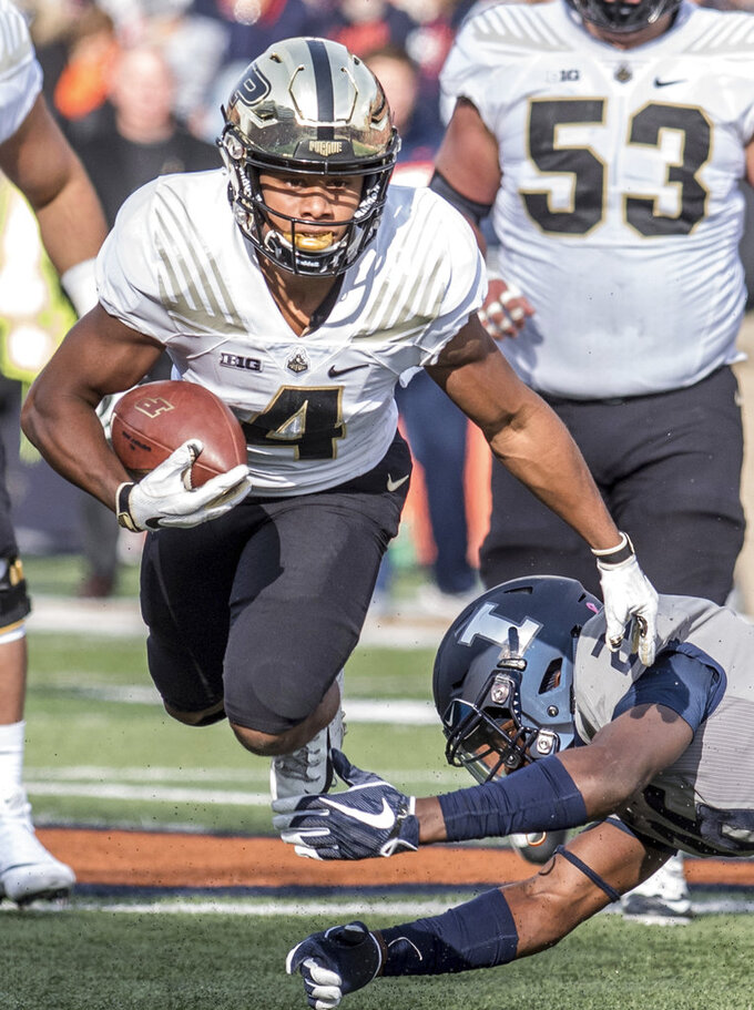 Purdue wide receiver Mondale Moore (4) runs as he avoids being tackled by Illinois' Kerby Joseph in the first half of an NCAA college football game, Saturday, Oct. 13, 2018, in Champaign, Ill. (AP Photo/Holly Hart)