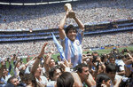 FILE - In this June 29, 1986, file photo, Diego Maradona holds up his team's trophy after Argentina's 3-2 victory over West Germany at the World Cup final soccer match at Azteca Stadium in Mexico City. Sports in 2020 was an unending state of mourning. Maradona died from a heart attack in Argentina weeks after brain surgery, the waves of grief rippling across soccer. (AP Photo/Carlo Fumagalli, File)