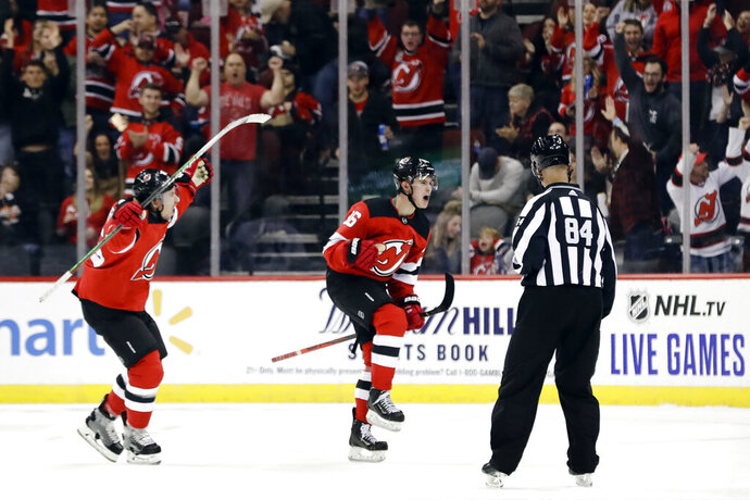 New Jersey Devils' Jack Hughes, center, celebrates with teammate Sami Vatanen, left, after scoring his first career NHL goal during the first period of a hockey game against the Vancouver Canucks, Saturday, Oct. 19, 2019, in Newark, N.J. (AP Photo/Frank Franklin II)