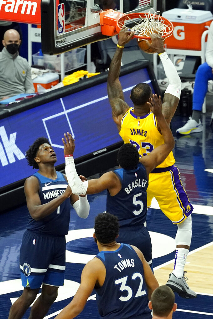 Los Angeles Lakers' LeBron James (23) dunks as Minnesota Timberwolves' Anthony Edwards (1),Malik Beasley (5) and Karl-Anthony Towns (32) watch in the first half of an NBA basketball game, Tuesday, Feb. 16, 2021, in Minneapolis. (AP Photo/Jim Mone)