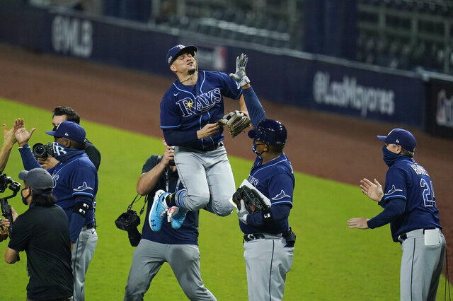 Tampa Bay Rays shortstop Willy Adames (1) jumps in the air while celebrating with teammates after defeating the New York Yankees in Game 3 of a baseball American League Division Series, Wednesday, Oct. 7, 2020, in San Diego. (AP Photo/Gregory Bull)