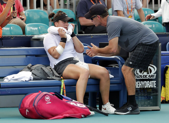 FILE - In this March 21, 2019 file photo, Bianca Andreescu, of Canada, left, talks with her coach Sylvain Bruneau during her match against Irina Camelia Begu, of Romania, at the Miami Open tennis tournament in Miami Gardens, Fla. Bruneau has released a statement, Sunday, Jan. 17, 2021, saying he was the positive coronavirus case aboard the flight from Abu Dhabi to Melbourne and he had followed all protocols and procedures, including producing a negative test within 72 hours before the flight departure and has