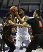 TCU center Kevin Samuel (21) shoots between Sam Houston State forward Kai Mitchell (20) and guard Albert Almanza (0) during the first half of an NCAA college basketball game in the NIT on Wednesday, March 20, 2019, in Fort Worth, Texas. (David Kent/Star-Telegram via AP)