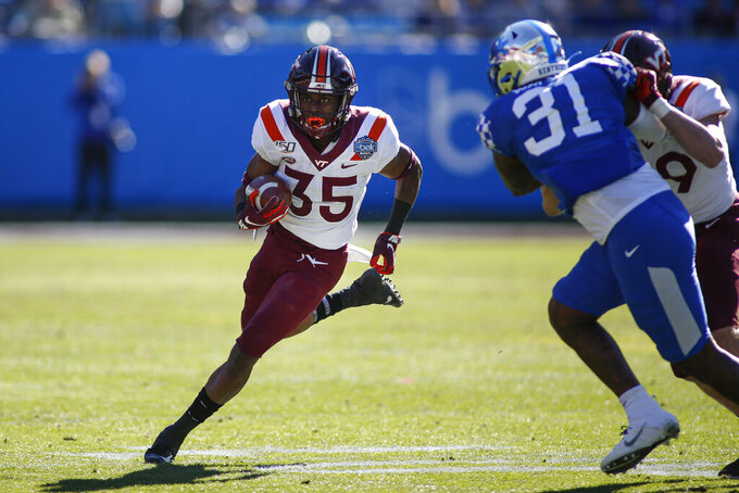 Virginia Tech running back Keshawn King, left, carries the ball as Kentucky linebacker Jamar Watson (31) pursues in the first half of the Belk Bowl NCAA college football game in Charlotte, N.C., Tuesday, Dec. 31, 2019. (AP Photo/Nell Redmond)