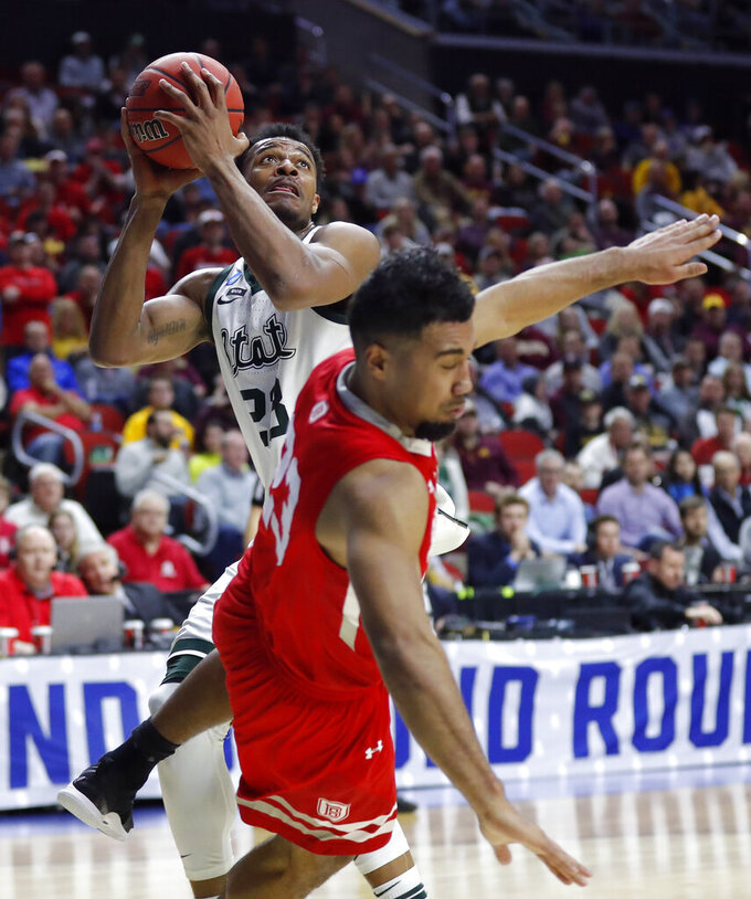 Michigan State forward Xavier Tillman, left, shoots over Bradley guard Dwayne Lautier-Ogunleye during a first round men's college basketball game in the NCAA Tournament, Thursday, March 21, 2019, in Des Moines, Iowa. (AP Photo/Charlie Neibergall)
