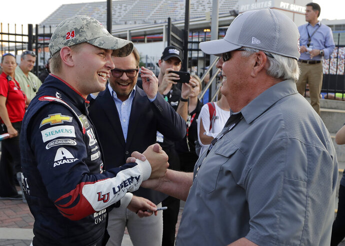 William Byron, left, is congratulated by team owner Rick Hendrick after winning the pole position during qualifying for Sunday's NASCAR Cup Series auto race at Charlotte Motor Speedway in Concord, N.C., Thursday, May 23, 2019. (AP Photo/Chuck Burton)
