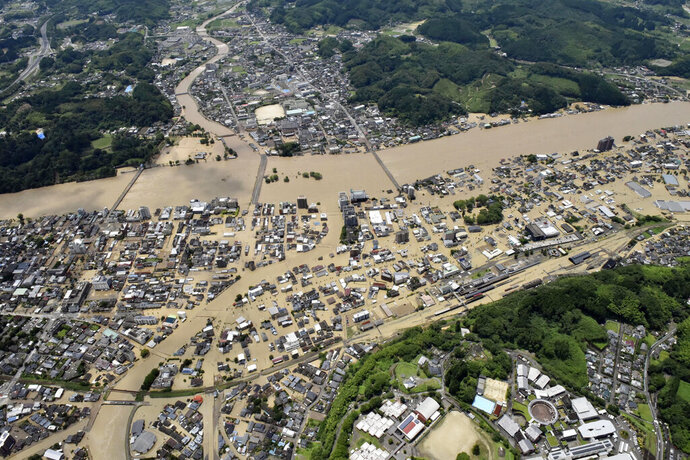 Areas are inundated in muddy waters that gushed out from the Kuma River in Hitoyoshi, Kumamoto prefecture, southwestern Japan, Saturday, July 4, 2020. Heavy rain triggered flooding and mudslides on Saturday, leaving more than a dozen missing and others stranded on rooftops waiting to be rescued. More than 75,000 residents in the prefectures of Kumamoto and Kagoshima were asked to evacuate following pounding rains overnight. (Kyodo News via AP)