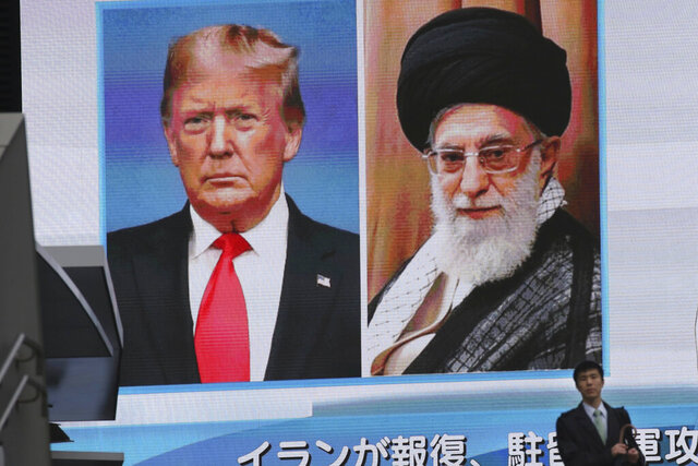 A man walks by a huge screen showing U.S. President Donald Trump, left, and Iranian Supreme Leader Ayatollah Ali Khamenei, in Tokyo, Wednesday, Jan. 8, 2020. Iran struck back at the United States early Wednesday for killing a top Revolutionary Guards commander, firing a series of ballistic missiles at two military bases in Iraq housing American troops in a major escalation between the two longtime foes. (AP Photo/Koji Sasahara)