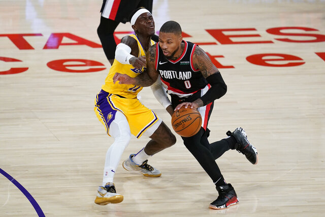 Portland Trail Blazers guard Damian Lillard, right, fouls Los Angeles Lakers guard Dennis Schroeder (17) during the second quarter of an NBA basketball game Monday, Dec. 28, 2020, in Los Angeles. (AP Photo/Ashley Landis)