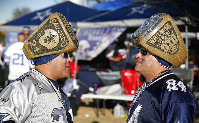 Chris and Steven Saucedo, from left, of San Antonio, Texas, speak before a NFC wild-card NFL football game between the Dallas Cowboys and the Seattle Seahawks in Arlington, Texas, Saturday, Jan. 5, 2019. (AP Photo/Michael Ainsworth)