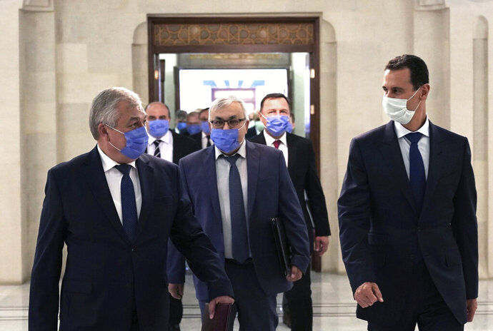 This photo provided by the official Facebook page of the Syrian Presidency, shows Syrian President Bashar Assad, right, and Russia's special presidential envoy to Syria Alexander Lavrentiev, left, both wearing masks to help prevent the spread of the coronavirus, in Damascus, Syria, Wednesday, July 29, 2020. (Syrian Presidency Facebook page via AP)