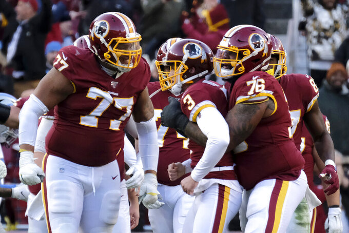 Washington Redskins kicker Dustin Hopkins (3) is congratulated by offensive guard Ereck Flowers (77) and offensive tackle Morgan Moses (76) after kicking a field goal against the Detroit Lions during the second half of an NFL football game, Sunday, Nov. 24, 2019, in Landover, Md. (AP Photo/Mark Tenally)