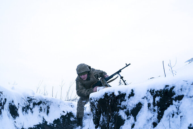 A Ukrainian serviceman changes his position near the line of contact near Vodiane, about 750 kilometers (468 miles) south-east of Kyiv, eastern Ukraine, Saturday, March 5, 2021. The country designated 14,000 doses of its first vaccine shipment for the military, especially those fighting Russia-backed separatists in the east. Ukrainians are becoming increasingly opposed to vaccination: an opinion poll this month by the Kyiv International Institute of Sociology found 60% of the country's people don't want to get vaccinated, up from 40% a month earlier. (AP Photo/Evgeniy Maloletka)