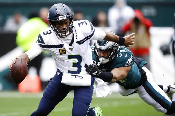 Seattle Seahawks' Russell Wilson (3) tries to slip past Philadelphia Eagles' Kamu Grugier-Hill (54) during the first half of an NFL football game, Sunday, Nov. 24, 2019, in Philadelphia. (AP Photo/Matt Rourke)