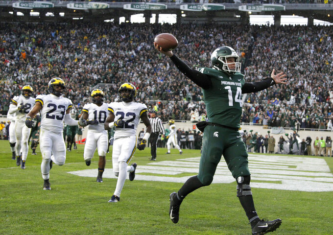FILE - In this Oct. 20, 2018, file photo, Michigan State quarterback Brian Lewerke, right, celebrates after making a touchdown reception during the third quarter against Michigan in an NCAA college football game in East Lansing, Mich. Michigan State plays Oregon in the Redbox Bowl on Monday. The time off before the bowl did a lot for Lewerke, who missed three games down the stretch with a shoulder injury. Coach Mark Dantonio said Lewerke's arm strength is back and he will start the bowl game. (AP Photo/Al Goldis, File)