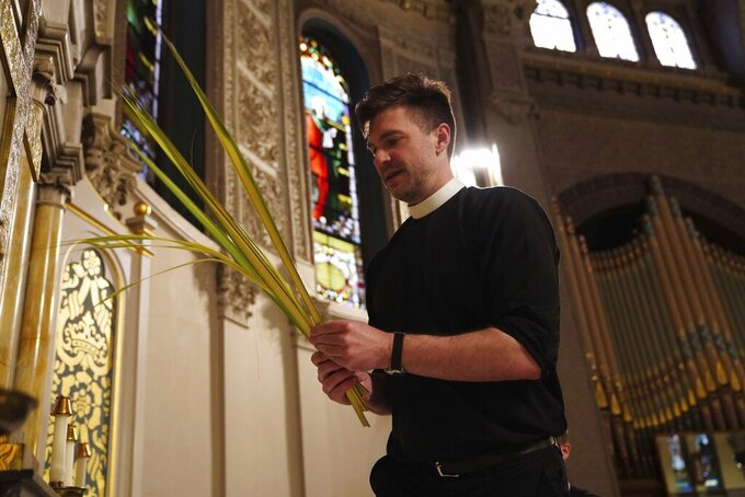In this Sunday, March 29, 2020 photo, Rev. Steven Paulikas decorates an altar with palm fronds for Palm Sunday, which will be commemorated virtually this year, at All Saints' Episcopal Church in the Brooklyn borough of New York. The global coronavirus pandemic is upending the season's major religious holidays, forcing leaders and practitioners across faiths to improvise. (AP Photo/Emily Leshner)