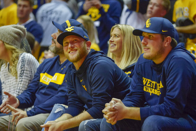 Country music singer and songwriter Cole Swindell reacts as one of his songs is played over the loudspeaker during the second half of an NCAA college basketball game between the West Virginia University Mountaineers and the University of Texas Longhorns in Morgantown, W.Va. on Saturday Feb. 9, 2019. (AP Photo/Craig Hudson)