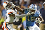 North Carolina running back Ty Chandler (19) runs the ball while Virginia defensive back Antonio Clary grabs his face mask during the second half of an NCAA college football game in Chapel Hill, N.C., Saturday, Sept. 18, 2021. (AP Photo/Gerry Broome)