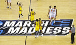 FILE - In this March 16, 2018, file photo, UMBC players celebrate their 74-54 win over Virginia in a first-round game in the NCAA men's college basketball tournament in Charlotte, N.C. This season's tournament, like all before them, would've been filled with dozens of legends in the making and diamonds in the rough--with teams that overcame adversity to get this far and superfans who inspired the country every bit as much as their team. (AP Photo/Chuck Burton, File)