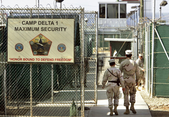 FILE - In this June 27, 2006, file photo, reviewed by a U.S. Department of Defense official, U.S. military guards walk within Camp Delta military-run prison, at the Guantanamo Bay U.S. Naval Base, Cuba. A federal judge has turned back an effort to delay an independent medical review for Saudi citizen Mohammed al-Qahtani, held at the Guantanamo Bay detention center who was so badly mistreated in American custody that he cannot be put on trial.  (AP Photo/Brennan Linsley, File)