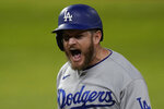 Los Angeles Dodgers' Max Muncy celebrates after two-RBI single against the Tampa Bay Rays during the third inning in Game 3 of the baseball World Series Friday, Oct. 23, 2020, in Arlington, Texas. (AP Photo/Eric Gay)