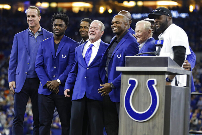 Former Indianapolis Colts defensive end Dwight Freeney, center right, and Colts owner Jim Irsay, center left, pose with other members of the teams' Ring of Honor, including Peyton Manning, left, and Edgerrin James, during Freeney's induction ceremony at half time of an NFL football game against the Miami Dolphins in Indianapolis, Sunday, Nov. 10, 2019. (AP Photo/Darron Cummings)