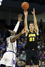 Iowa forward Nicholas Baer, right, shoots over Northwestern forward Vic Law during the first half of an NCAA college basketball game Wednesday, Jan. 9, 2019, in Evanston, Ill. (AP Photo/Nam Y. Huh)