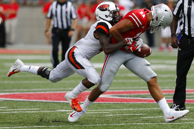 Oregon State defensive back Dwayne Williams, left, tackles Ohio State receiver Austin Mack during the second half of an NCAA college football game Saturday, Sept. 1, 2018, in Columbus, Ohio. Ohio State beat Oregon State 77-31. (AP Photo/Jay LaPrete)