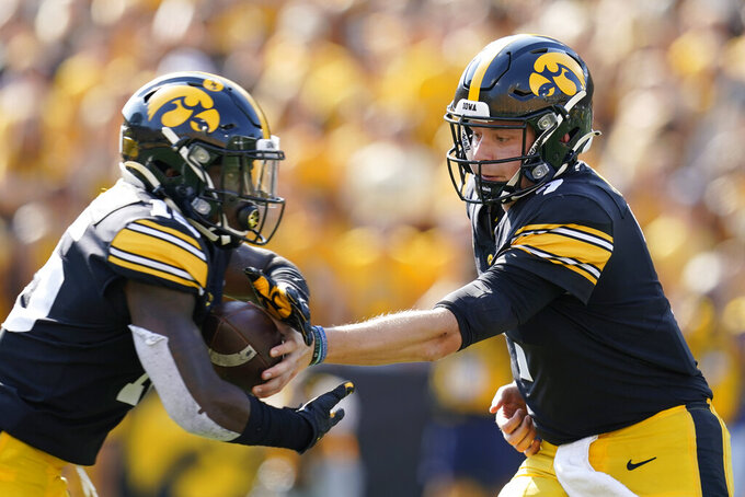 Iowa quarterback Spencer Petras hands the ball off to running back Tyler Goodson, left, during the first half of an NCAA college football game against Kent State, Saturday, Sept. 18, 2021, in Iowa City, Iowa. Iowa won 30-7. (AP Photo/Charlie Neibergall)