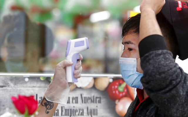 FILE - In this May 12, 2020 file photo, amid concerns of the spread of COVID-19, Ronaldo Santos has his temperature checked before starting his work shift in the meat department of a grocery store in Dallas. With more businesses across the country easing back to life, the new challenge will be how to keep workers safe during the pandemic. From temperature checks, contact tracing, social distancing and staggered schedules, a variety of new protocols are being implemented. (AP Photo/LM Otero)