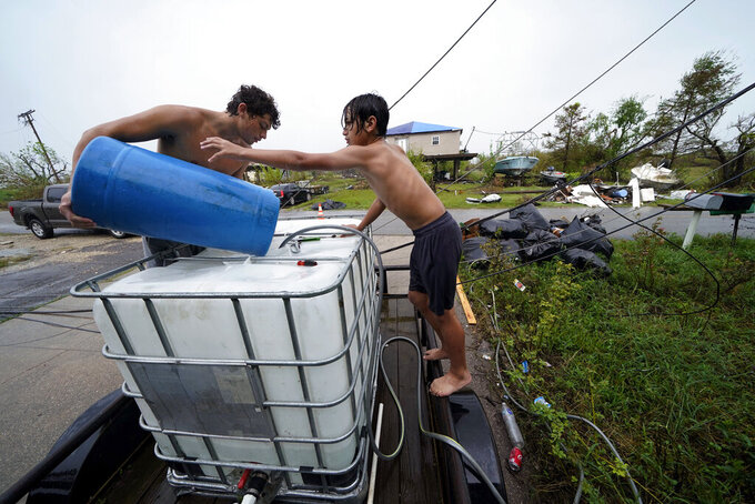 Terren Dardar, 17, left, and Dayton Verdin, 14, pour barrels of rainwater they collected from Tropical Storm Nicholas, in the aftermath of Hurricane Ida in Pointe-aux-Chenes, La., Tuesday, Sept. 14, 2021. They have had no running water since the hurricane, and collected 140 gallons of rainwater in two hours from the tropical storm, which they filter and pump into their house for showers. (AP Photo/Gerald Herbert)