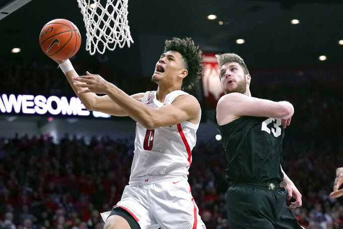Arizona guard Josh Green (0) drives past Colorado forward Lucas Siewert during the second half of an NCAA college basketball game Saturday, Jan. 18, 2020, in Tucson, Ariz. Arizona won 75-54. (AP Photo/Rick Scuteri)