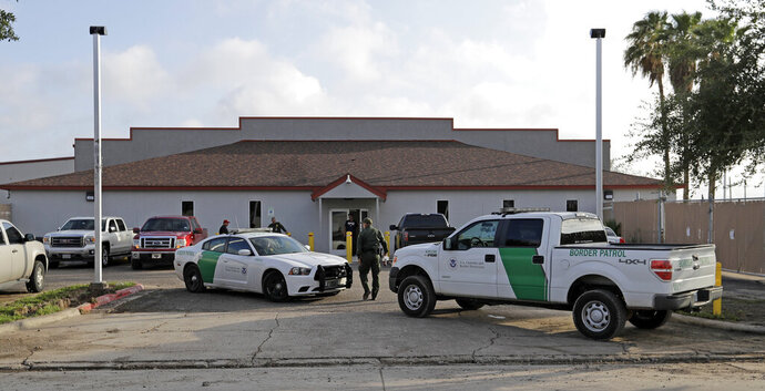 FILE - In this June 23, 2018 file photo, a U.S. Border Patrol Agent walks between vehicles outside the Central Processing Center in McAllen, Texas. U.S. border agents have temporarily closed their primary facility for processing migrants in South Texas one day after authorities say a 16-year-old died after being diagnosed with the flu at the facility. In a statement released late Tuesday, May 21, 2019, U.S. Customs and Border Protection said it would stop detaining migrants at the processing center in McAllen, Texas. CBP says