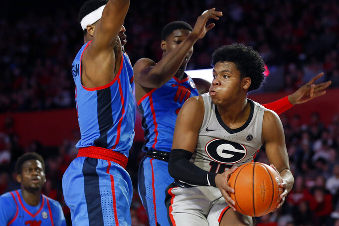 Georgia's Sahvir Wheeler (15) tries to find an open pass around Mississippi guard/forward Blake Hinson (0) and Mississippi guard Bryce Williams (13) during an NCAA college basketball game in Athens, Ga., Saturday, Jan. 25, 2020. (Joshua L. Jones/Athens Banner-Herald via AP)