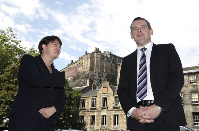 FILE - In this July 31, 2020 file photo, former Scottish Conservative leader Ruth Davidson, left and  Scottish Conservative MP Douglas Ross pose for a photo, in Edinburgh. Scotland's Conservative Party on Wednesday, Aug. 5, 2020, appointed Ross as their new leader to fight an election next year against a dominant Scottish Nationalist Party. Ross was a minister in Prime Minister Boris Johnson's U.K. government until he stepped down in May after Johnson adviser Dominic Cummings broke coronavirus lockdown rules by driving 250 miles (400 kilometers) to a family home. (Andrew Milligan/PA via AP, File)