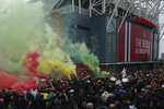 Manchester United fans let off flares as they protest against the Glazer family, the American owners of Manchester United, before their English Premier League soccer match against Liverpool at Old Trafford stadium in Manchester, England, Thursday, May 13, 2021. (AP Photo/Jon Super)