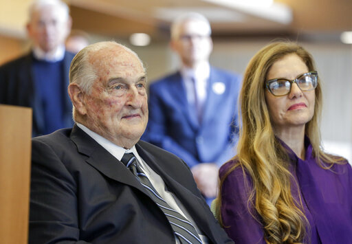 FILE - Philanthropist Walter Scott, left, sits next to Leslie Jackson, wife of glass artist Dale Chihuly during a ceremony at the Fred & Pamela Buffett Cancer Center in Omaha, Neb., Friday, May 19, 2017. Billionaire Scott, the past top executive of Peter Kiewit Sons Inc. construction firm who helped oversee Warren Buffett's conglomerate and donated to various causes, particularly construction projects around Omaha, died, Saturday, Sept. 25, 2021. He was 90. (AP Photo/Nati Harnik, File)