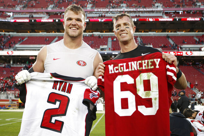 San Francisco 49ers offensive tackle Mike McGlinchey, left, poses for photos while exchanging jerseys with Atlanta Falcons quarterback Matt Ryan after an NFL football game in Santa Clara, Calif., Sunday, Dec. 15, 2019. (AP Photo/Josie Lepe)