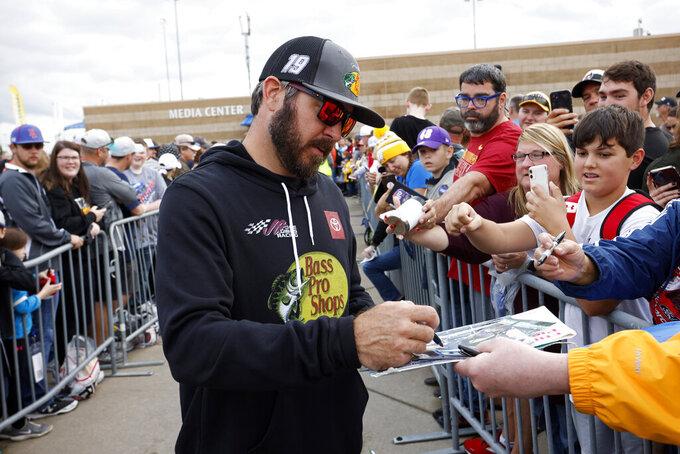 Martin Truex Jr. signs autographs before a NASCAR Cup Series auto race at Kansas Speedway in Kansas City, Kan., Sunday, Oct. 24, 2021. (AP Photo/Colin E. Braley)